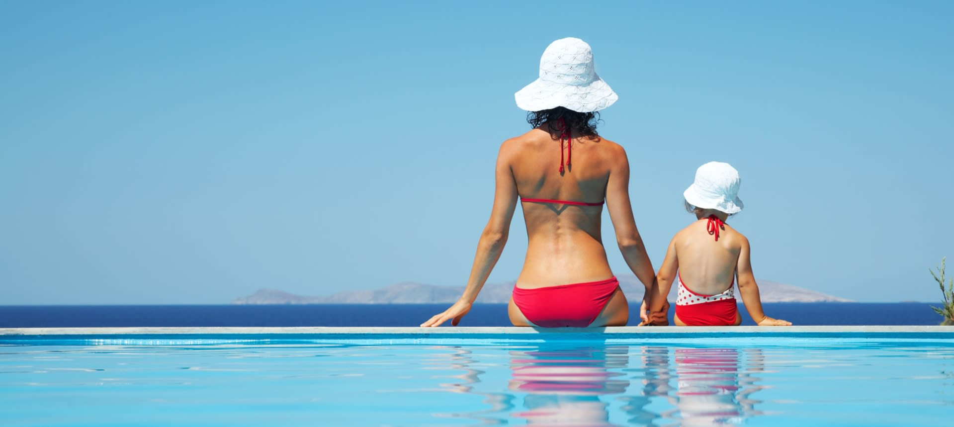 Mom and daughter sitting by the pool